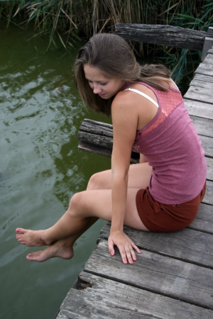Young blonde girl seating on wooden bridge at the river bank in background of cane