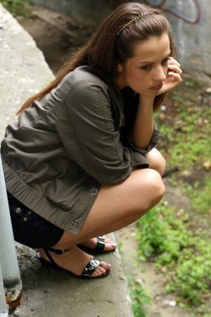 tied hair: Depresso giovane donna sedersi sul alto Archivio Fotografico