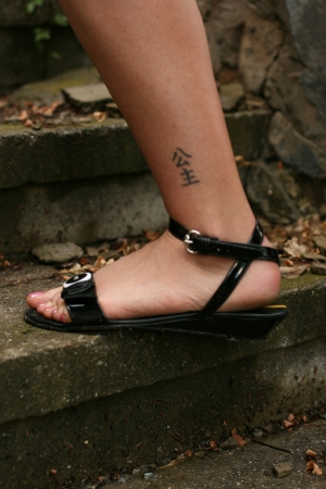 Female leg with hieroglyph tattoo, stay on stairs Stock Photo - 15317003