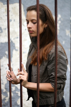 woman prison: Trapped girl behind iron bars Stock Photo