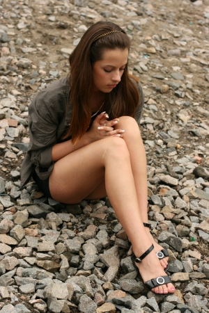 long feet: Thoughtful young girl sit on the river bank