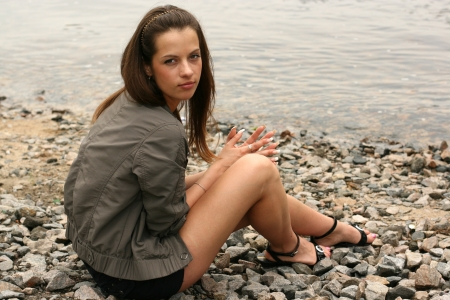 puberty: Thoughtful young girl sit on the river bank