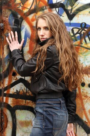 Urban style  Back of provocative predatory girl with long blonde hair on graffiti background Stock Photo