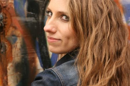 agressive: Urban style  Portrait of half-turn provocative predatory girl with long blonde hair on graffiti background