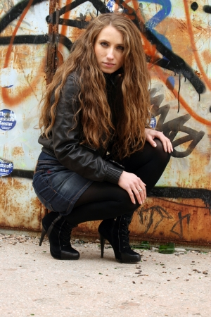 Urban style  Provocative predatory girl with long blonde hair on graffiti background Stock Photo