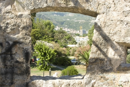 A window in the ramparts allows to see the hills around the city of Budva, Montenegro.