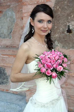 A lovely bride with bouquet from roses on background of peeling wall  Stock Photo - 15569224
