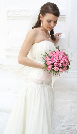 A lovely bride looks down at her bouquet from roses  She is dressed in a simple gown and wearing a veil  photo
