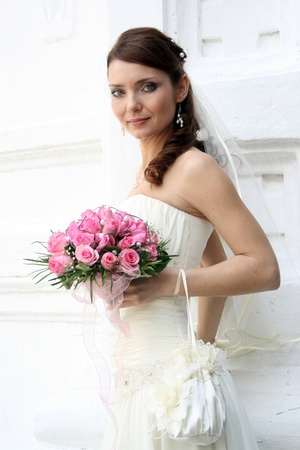 A lovely bride looks at the camera  She hold her bouquet from roses  And she dressed in a simple gown and wearing a veil  photo