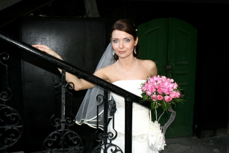 A lovely bride with bouquet from roses on black stairs  Green door behind her