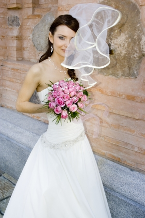 A lovely bride with bouquet from roses on background of peeling wall. Veil cover a half of her face. Stock Photo - 15574355