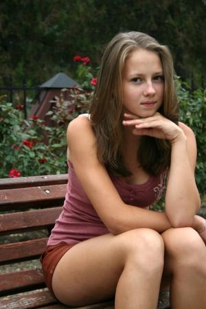 ragazza: Pretty girl in posti a sedere giardino di rose in panchina
