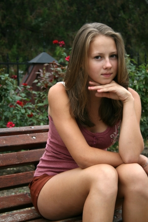 teenager girl: Pretty girl in rose garden seating on the bench