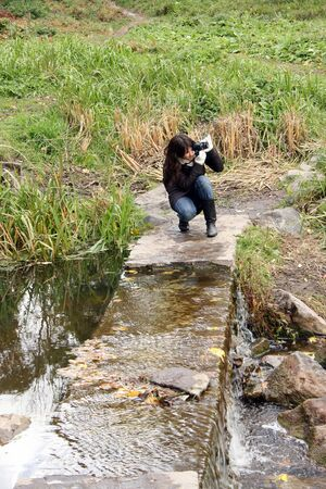 Woman photographer making photo squat Stock Photo
