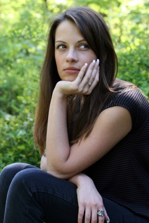brune: Portrait of beautiful dark-haired woman at summer green park  She resting her chin on her hand