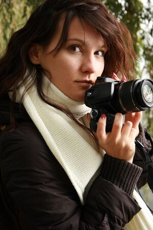 brune: Young woman holding a camera. Stock Photo