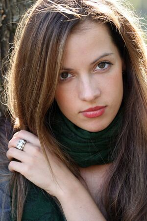 Portrait of young brunette woman in green scarf.