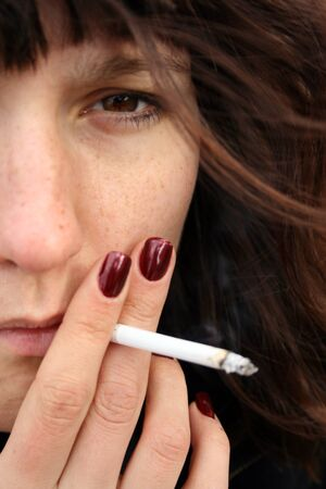 A girl with red nails smoking a cigarette. Close up of a young woman. Stock Photo