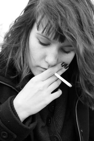 A girl with red nails smoking a cigarette  Close up black and white portrait of a young woman  photo