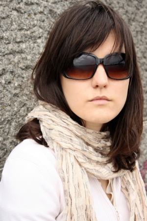 Woman in sunglasses on background of stony wall. She wearing in scarf. Stock Photo