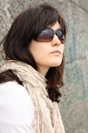 Woman in sunglasses on background of wall. She wearing in scarf.