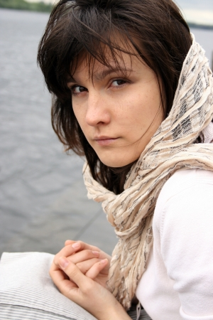 Portrait of beautiful haughty woman in scarf on her head on water background.