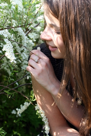 A young woman with long brunette hair smelling flower. Stock Photo - 15911156