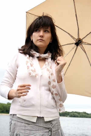 Isolated woman holding an umbrella. Concept of support, protection. She is on background of river. Stock Photo - 15937245