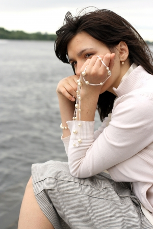 Portrait of beautiful woman with beads. She waiting somebody on the river bank. Stock Photo - 15937259