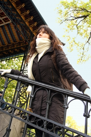 Portrait of young woman in scarf and gloves. Shes walking in autumn park. photo