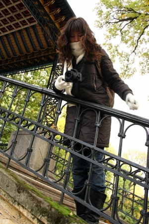 Portrait of young woman in scarf and gloves. Shes walking in autumn park.