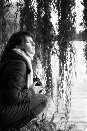 Portrait of young woman in scarf. She's setting on the river bank and dreaming. Black and white photo. photo