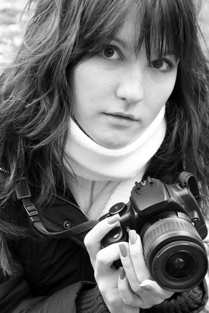 Close up portrait of young woman in scarf. Photographer hold camera. Black and white photo. photo