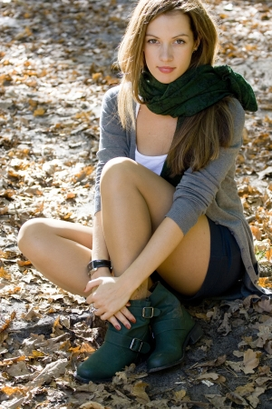 Young brunette woman portrait in autumn colors. Shes seating on the ground in autumn park.