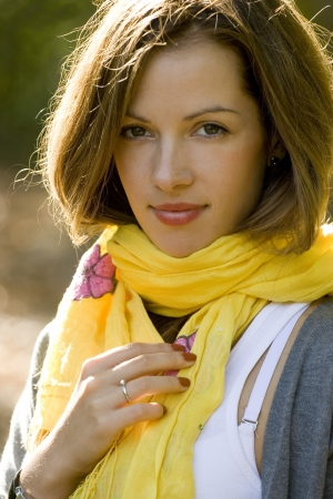 Portrait of young brunette woman in yellow scarf in autumn colors.  Stock Photo
