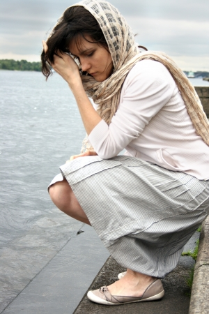 waterside: Beautiful sad woman sitting on waterside. Stock Photo