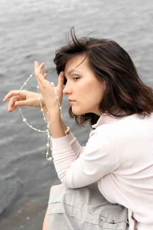 Portrait of beautiful woman with beads. She waiting somebody on the waterside.