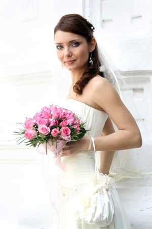 A lovely bride looks at the camera. She hold her bouquet from roses. And she dressed in a simple gown and wearing a veil. Stock Photo