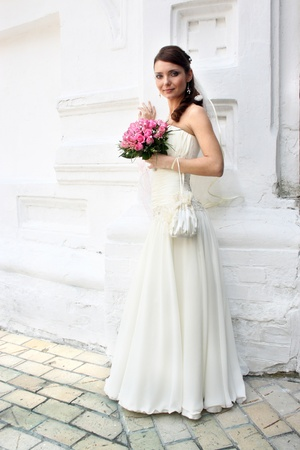 A lovely bride with bouquet from roses, looks at the camera. She is dressed in a simple gown and wearing a veil.