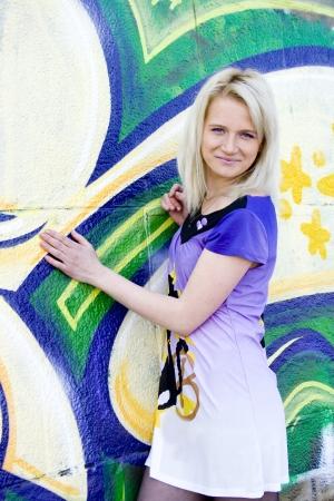 Beautiful woman with blonde hair on graffiti background.