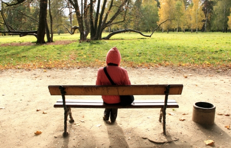 Lonely woman sitting on the bench in autumnal park.