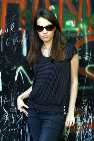 inscrutable: Woman in sunglasses on background of graffiti wall. Stock Photo