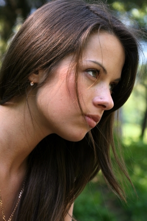 Woman with long brunette hair in profile.