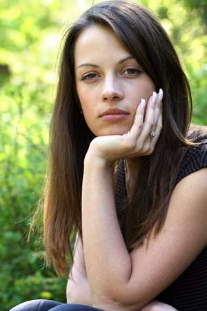 hand on chin: Woman with long brunette hair on natural green background. She rest her chin on her hand.