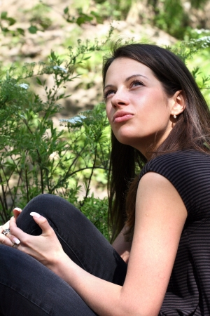 brune: Woman with long brunette hair in spring park. Shes looking up.