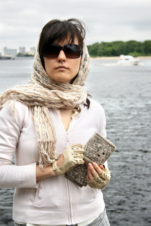 Woman in sunglasses and  kerchief on her head. She hold clutch. Retro style. photo