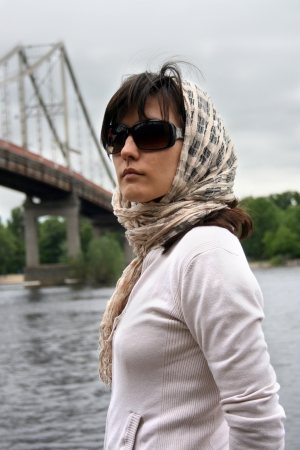 brune: Woman in sunglasses and kerchief on her head. She on background of bridge. Retro style.