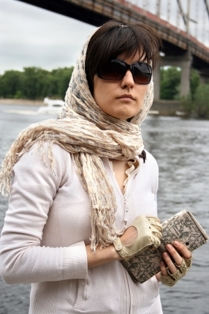 Woman in sunglasses and  kerchief on her head. She hold clutch. She on background of bridge. Retro style.