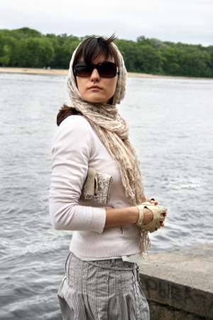 brune: Woman in sunglasses and  kerchief on her head. She hold clutch. Retro style.
