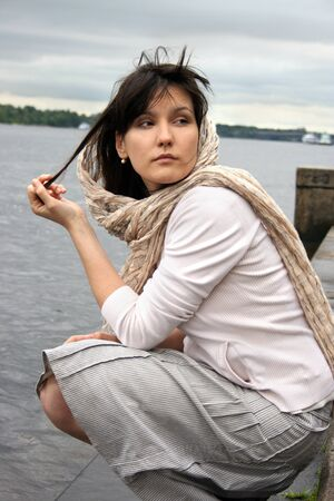 Woman in kerchief on her head. She sitting near waterside. Retro style. photo